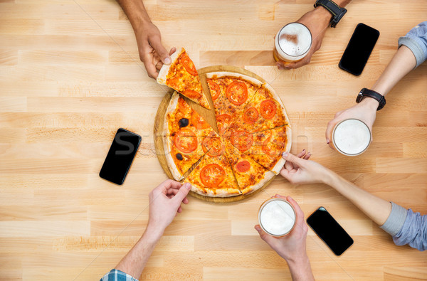 Group of students meeting and eating pizza together  Stock photo © deandrobot