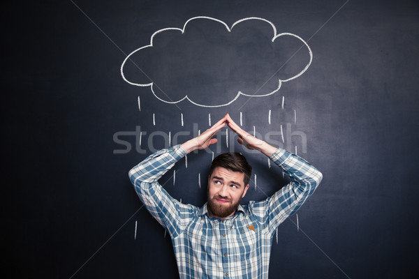 Frowning man covering from rain drawn on blackboard background Stock photo © deandrobot