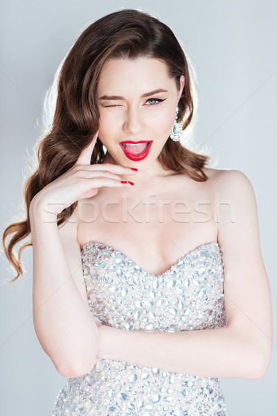 Cheerful woman in fashion dress winking  Stock photo © deandrobot