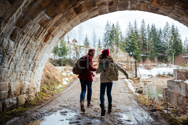 Couple holding hands and running together under the bridge Stock photo © deandrobot