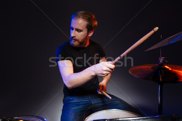 Bearded man drummer with closed eyes sitting and playing drums  Stock photo © deandrobot