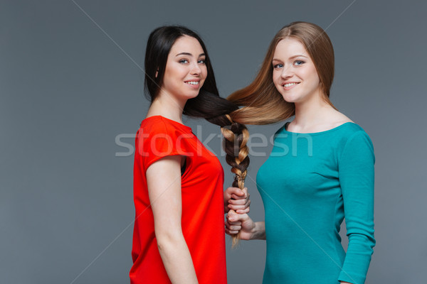 Two happy young women made one brair with their hair Stock photo © deandrobot