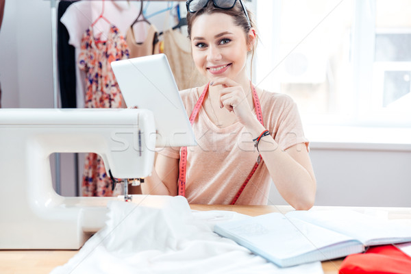 Cheerful woman seamstress smiling and using tablet at work Stock photo © deandrobot
