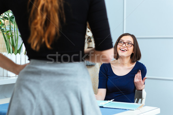 Cheerful woman talking to waitress and making order in cafe Stock photo © deandrobot