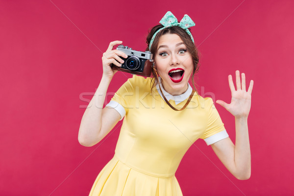 Cheerful pinup girl using vintage camera and taking pictures Stock photo © deandrobot
