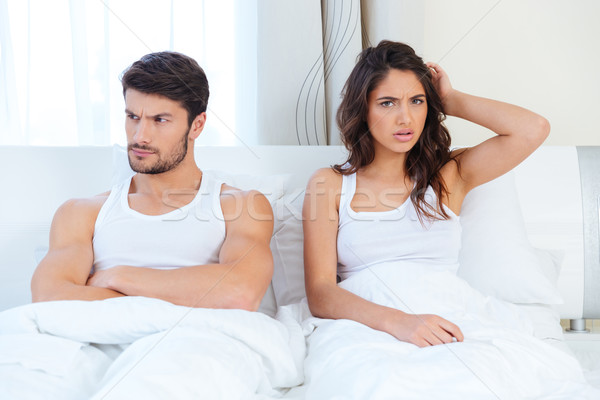 Unhappy separate couple lying in a bed Stock photo © deandrobot