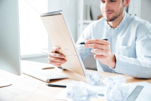 Uśmiechnięty młodych biznesmen posiedzenia piśmie notatnika Zdjęcia stock © deandrobot