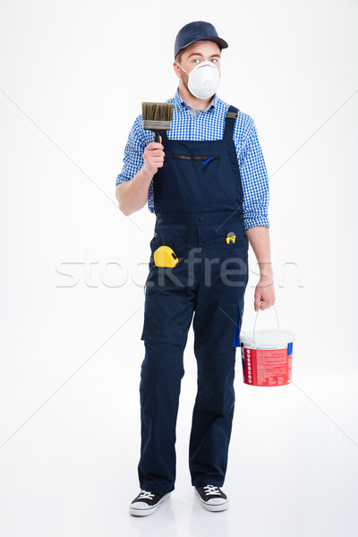 Man painter in protective mask holding paint bucket and brush Stock photo © deandrobot
