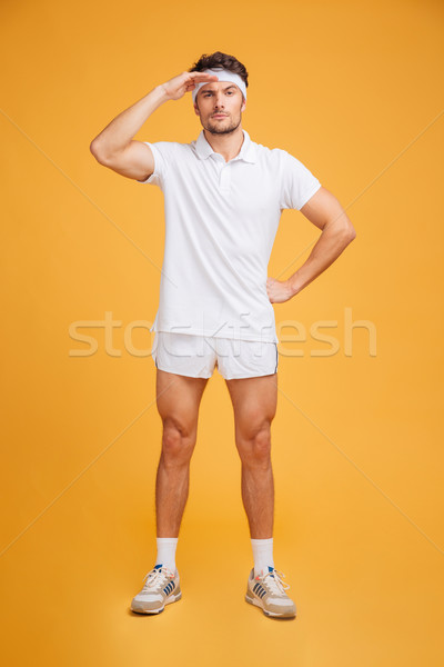 Serious handsome young sportsman standing and looking fr away Stock photo © deandrobot
