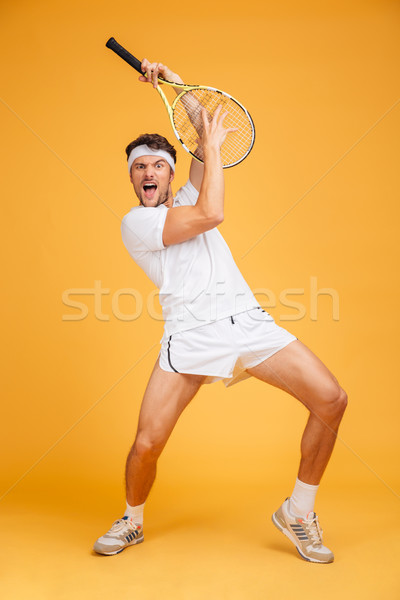 Comical playful young man tennis player with racket having fun Stock photo © deandrobot