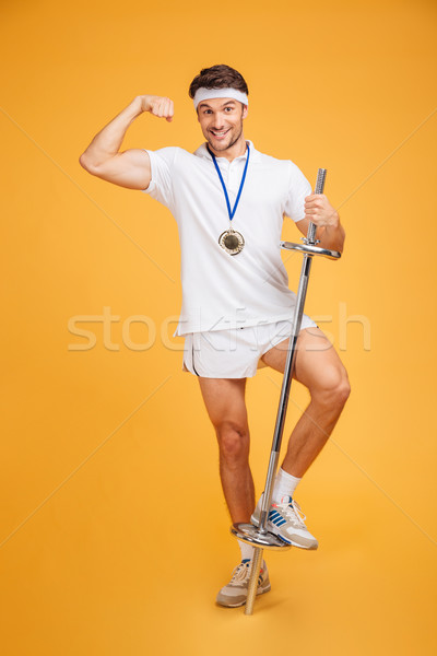 Smiling young fitness man showing biceps and holding barbell Stock photo © deandrobot