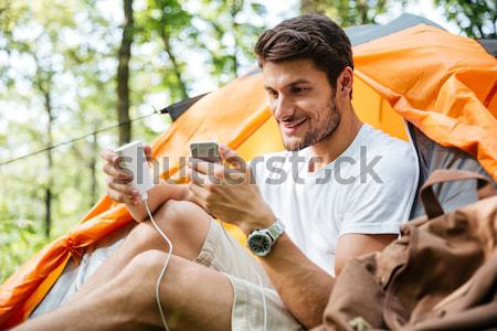 Man tourist using cell phone and portable mini speaker Stock photo © deandrobot