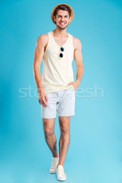 Uśmiechnięty młody człowiek hat szorty spaceru moda Zdjęcia stock © deandrobot