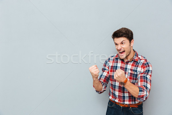 Angry mad man in plaid shirt showing fists and shouting Stock photo © deandrobot