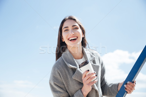 Portrait of a young smiling girl holding take away cup Stock photo © deandrobot