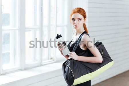 Young woman with bottle of water and sports bag Stock photo © deandrobot