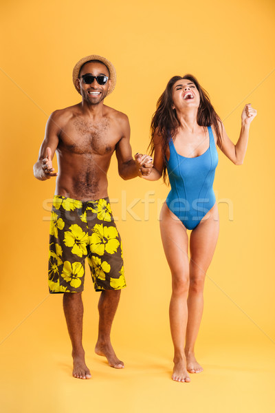 Young beautiful happy cheerful couple in beachwear holding hands Stock photo © deandrobot