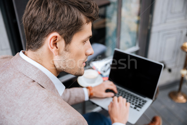 Closeup of serious businessman using modern laptop in coffee shop Stock photo © deandrobot