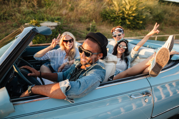 Smiling friends driving car and showing peace sign in summer Stock photo © deandrobot