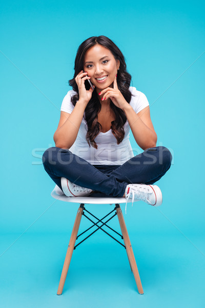 Happy young vietnamese woman talking on the phone Stock photo © deandrobot
