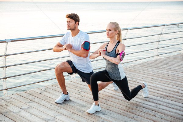 Athletic young couple sitting and stretching legs together Stock photo © deandrobot