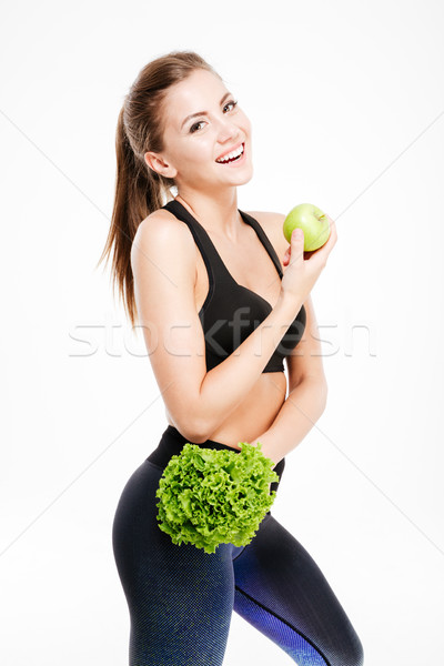 Smiling fitness woman holding apple and lettuce Stock photo © deandrobot