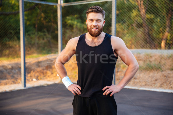 Happy young man in sportswear standing with hands on hips Stock photo © deandrobot