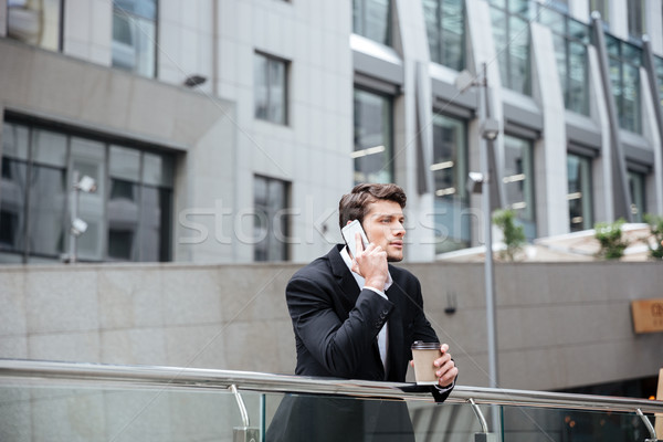 Businessman talking on mobile phone and drinking coffee in city Stock photo © deandrobot