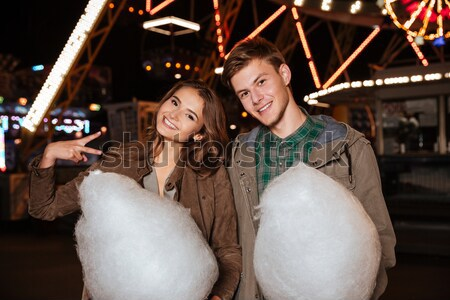 Stock photo: Couple holding cotton candy standing in amusment park