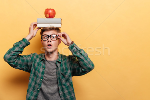 Stock photo: Astonished man student with book and apple on his head