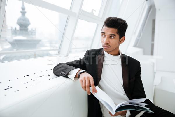 Zamyślony Afryki człowiek biznesu młodych czarny garnitur posiedzenia Zdjęcia stock © deandrobot