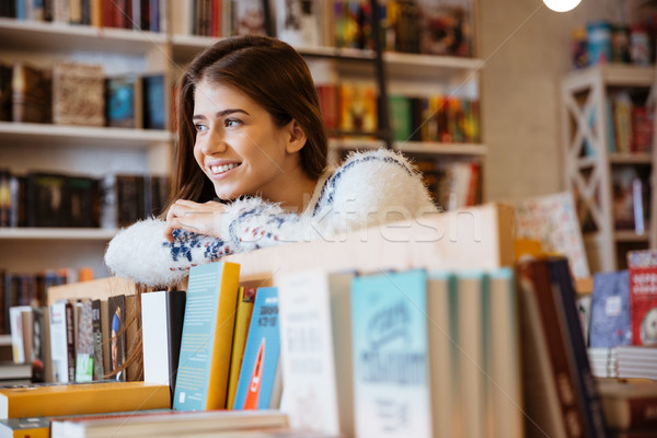 Young female student choosing books in library Stock photo © deandrobot
