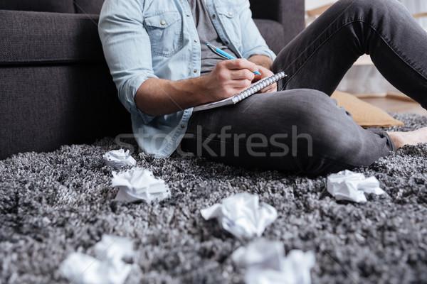Człowiek zauważa notatnika posiedzenia dywan Zdjęcia stock © deandrobot
