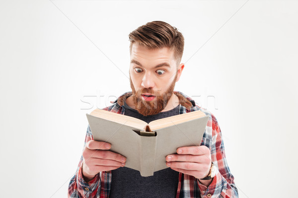 Young beraded man looking in book with eyes wide open Stock photo © deandrobot