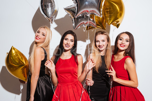 Four cheerful young women standing and holding star shaped balloons Stock photo © deandrobot