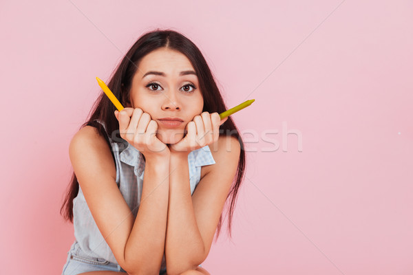 Confused young woman holding crayons and looking at camera Stock photo © deandrobot