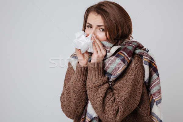 Sick young woman with napkin over gray background. Stock photo © deandrobot