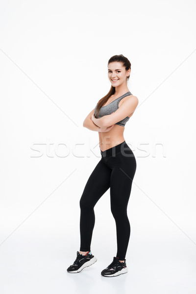 Portrait of a happy fitness woman standing with arms folded Stock photo © deandrobot