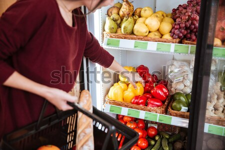 Woman choosing fruits and using cell phone in grocery shop Stock photo © deandrobot