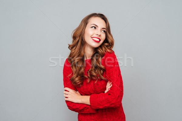 Smiling woman in red sweater looking away Stock photo © deandrobot