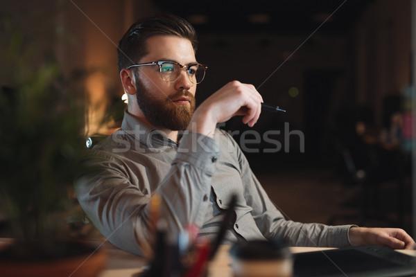 Concentrato barbuto web designer guardando computer Foto d'archivio © deandrobot