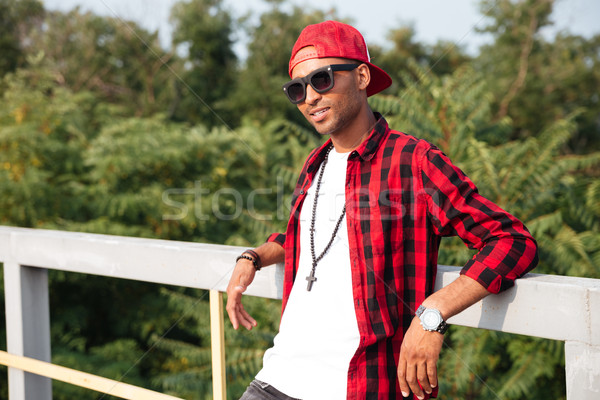 Young attractive dark skinned guy with trees on background Stock photo © deandrobot