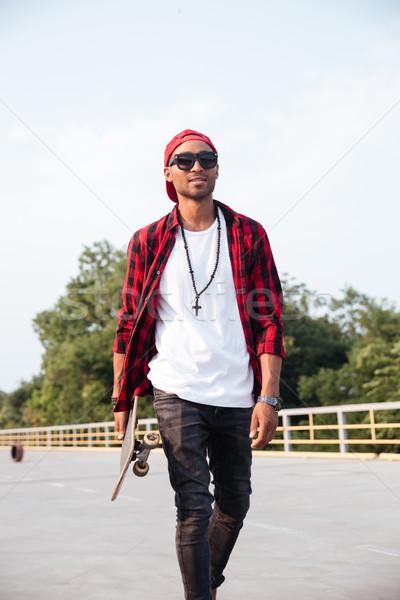Young dark skinned boy holding skateboard Stock photo © deandrobot