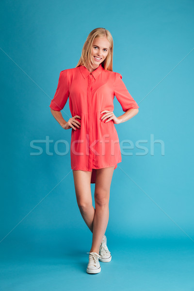 Smiling woman in red dress standing with hands on hips Stock photo © deandrobot