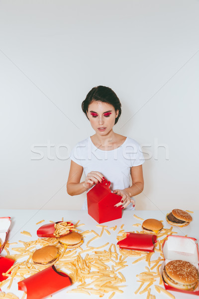 Attractive woman sitting and eating fast food from red box Stock photo © deandrobot