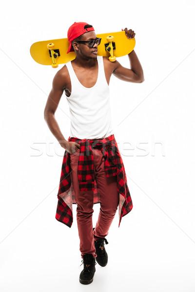 Africaine jeune homme cap lunettes de soleil skateboard Photo stock © deandrobot