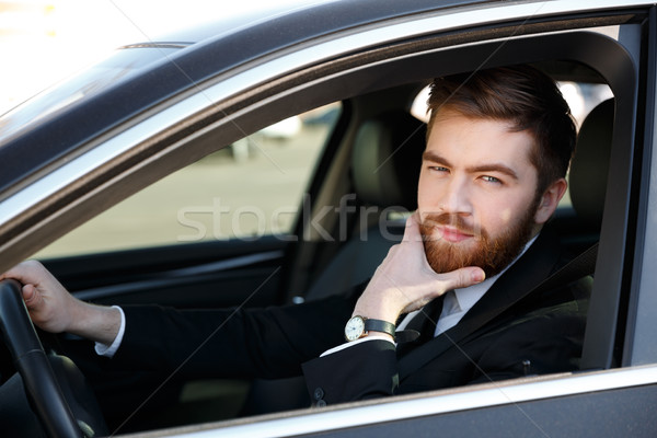 Pensive business man holding hand on chin and driving car Stock photo © deandrobot