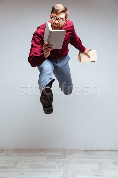 Vertical image of Male nerd jumping with books Stock photo © deandrobot