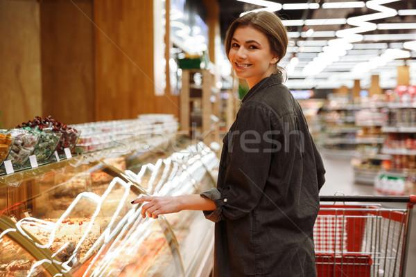 Boldog hölgy áll áruház választ sütemények Stock fotó © deandrobot