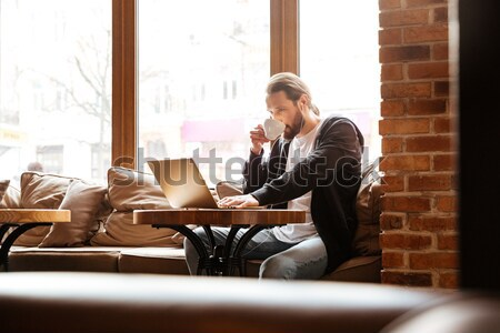 Bearded man with laptop drinking coffee in cafe Stock photo © deandrobot